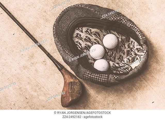 Old-fashion artistic still life photo on golfing gear including a flat cap, golf balls and club. Antique golfer still life