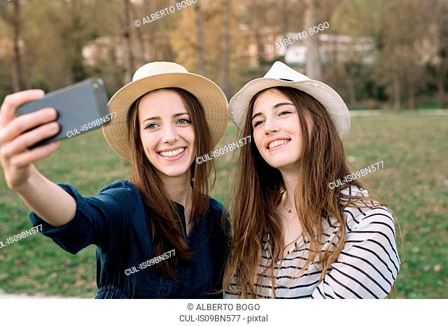 Girlfriends taking selfie in park