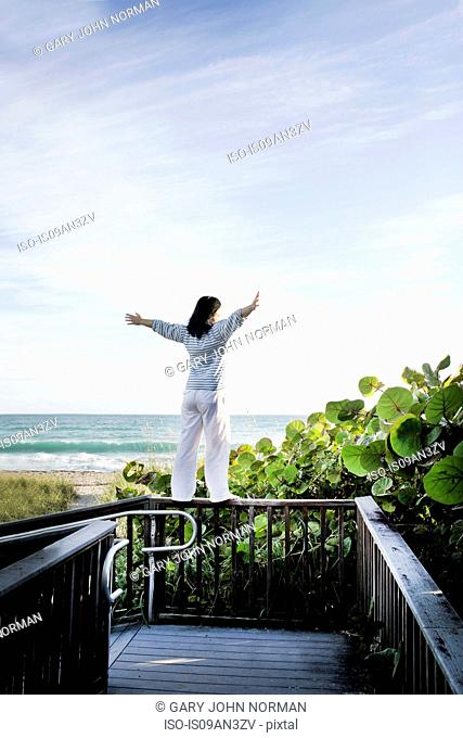 Mature woman with arms open on top of walkway railing, Juno Beach, Florida, USA