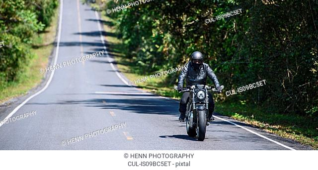 Motorcyclist riding on tree lined road, Khao Yai national park, Prachin Buri, Thailand