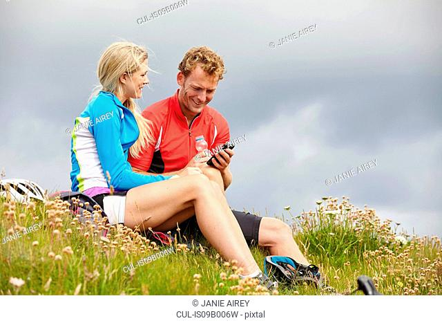Cyclists relaxing and chatting on grassy hilltop