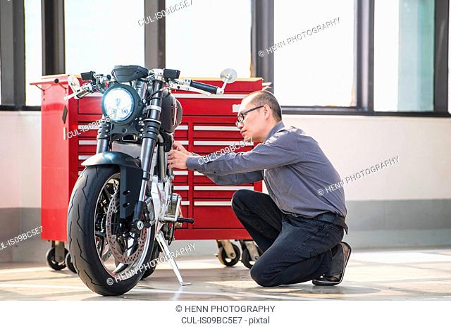 Technician in garage, checking electric cafe racer motorbike