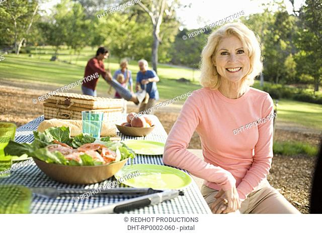 Grandparents and family in park with picnic