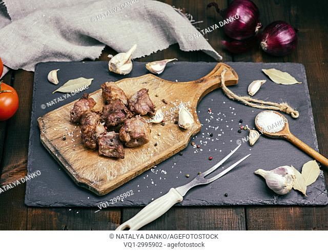 pieces of fried pork on a brown wooden board with spices, top view, vintage toning
