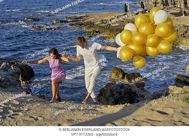 couple walking together at beach, holding hands, holding balloons