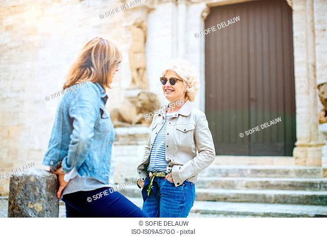 Two mature female friends talking in front of historic building, Tuscany, Italy