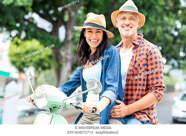 Portrait of happy couple on moped