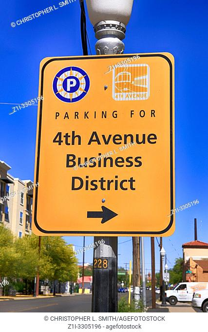 A bright yellow direction sign for parking in the 4th Avenue Business District of Tucson AZ
