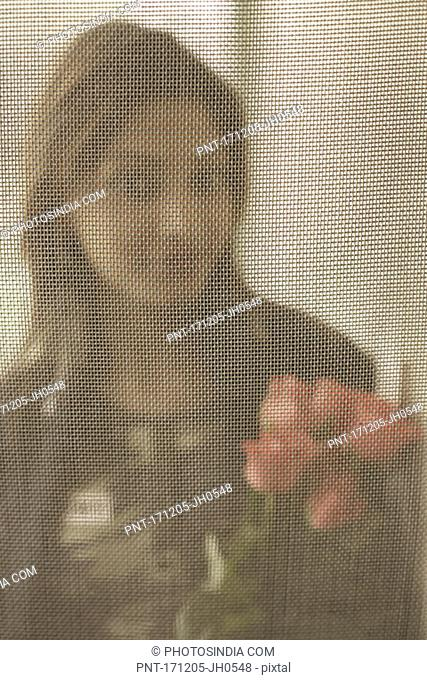 Portrait of a young woman looking through a net