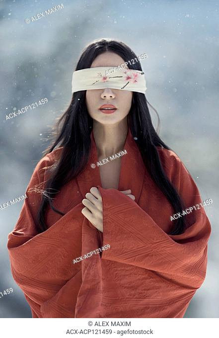 Artistic portrait of a beautiful asian woman with red sensual lips wearing a red undone kimono standing in the snow with a long black hair and a blindfold over...