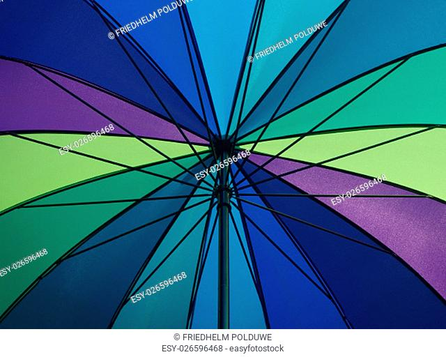 Detail of a colorful opened umbrella watched from underneath while sunshine