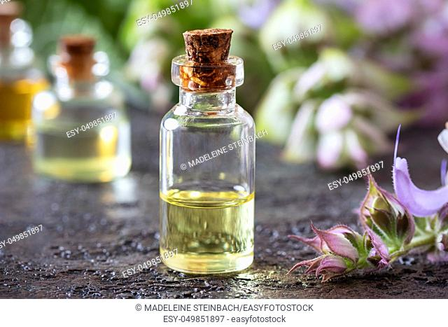 A bottle of essential oil with blooming clary sage twigs on a dark background