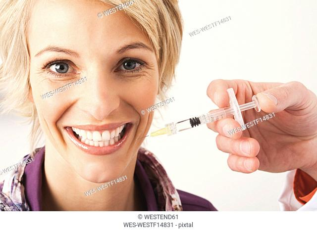 Germany, Munich, Doctor giving Botox treatment to woman