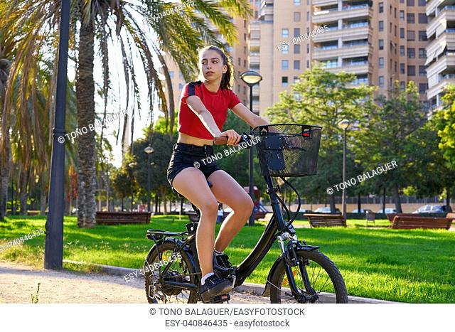 Girl riding e-bike in a city park with red t-shirt foldable ebike