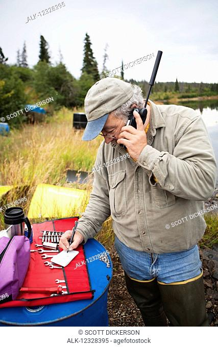Person On A Satellite Phone During A Remote Moose Hunt, Lake Iliamna, Southwest Alaska, USA