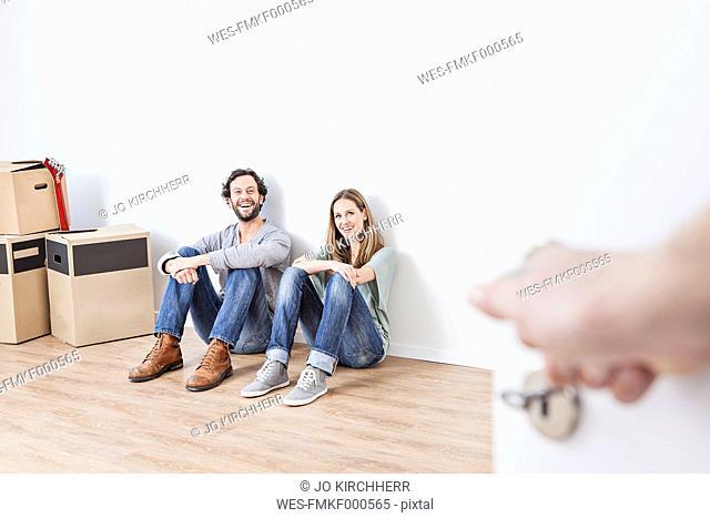 Couple sitting on floor, smiling