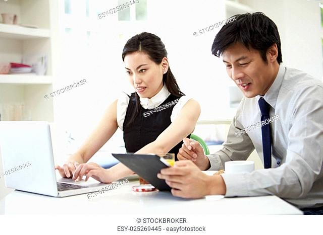 Asian Couple Using Digital Devices At Breakfast Table