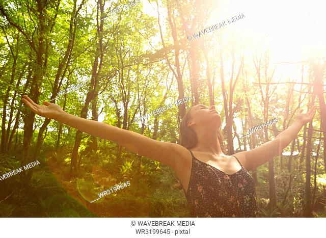Woman with hands spread standing below bright sunlight