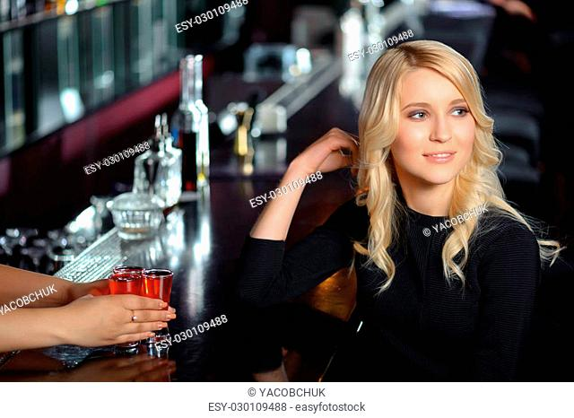 Nightclub. Portrait of a beautiful blonde girl sitting by the bar counter and having a drink