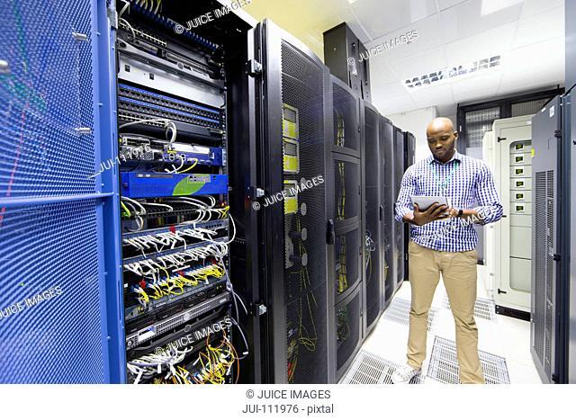 Technician checking digital tablet in server data centre
