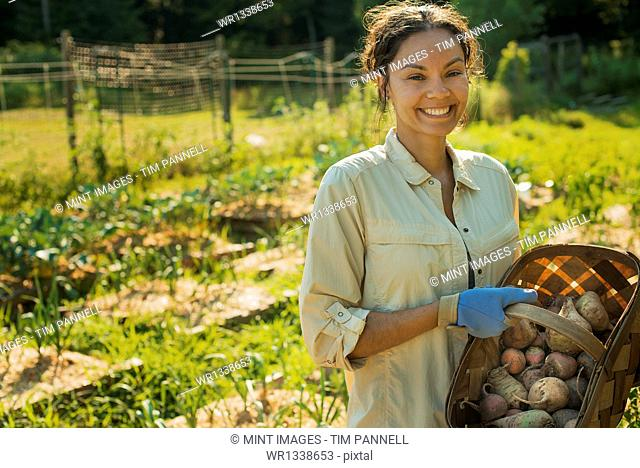 A woman carrying a basket of freshly gathered vegetables and root crops