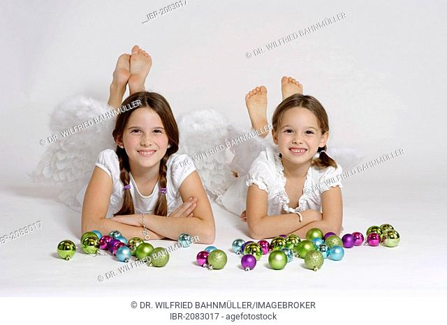 Two girls dressed up as Christmas angel, Christ Child with Christmas baubles
