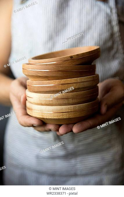 A woodworker holding a stack of turned wood bowls or dishes