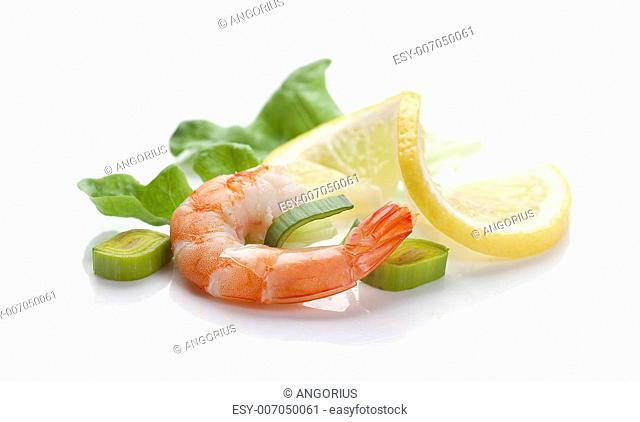 One boiled shrimp's tail with lettuce, leek and lemon on the white