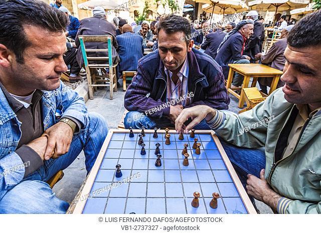Kurdish men playing draughts at Gumruk Hanı caravanserai. Old bazaar of Urfa, Southeast Turkey
