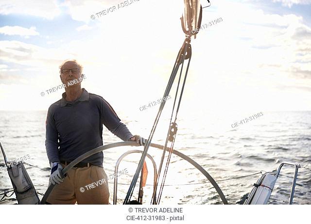 Retired man sailing steering sailboat at helm