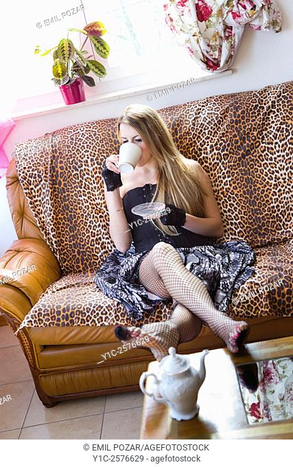 Young woman is drinking tea on sofa