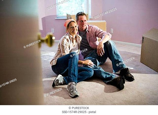 Cheerful mid adult couple sitting by cardboard boxes in a house