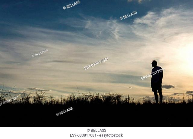Man in silhouette standing on hill looking out at view