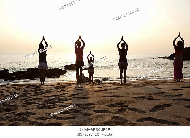 Women practicing yoga on beach at sunset