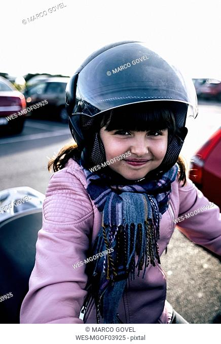Portrait of smiling little girl on a motorcycle wearing helmet and pink leather jacket