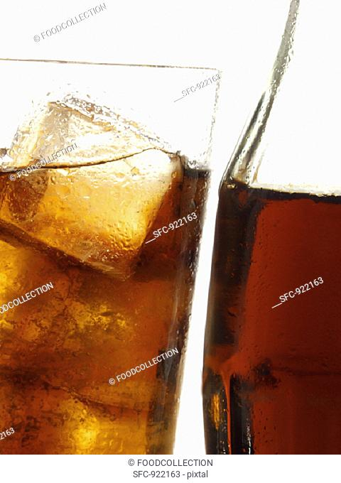 Cola in bottle and glass with ice cubes (close-up)