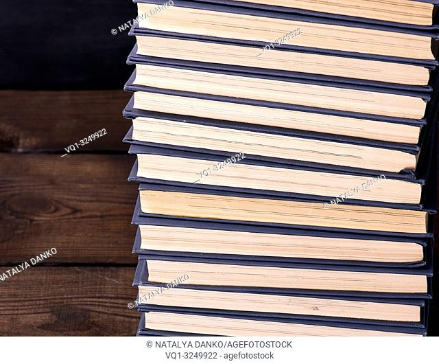 large stack of books in a blue cover on a brown wooden table
