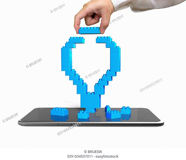 Human hand holding a blue block to complete light bulb shape with smart phone, isolated on white background