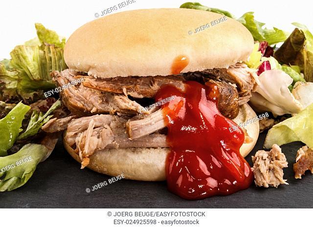 hamburger with pulled pork, fresh healthy salad and ketchup on slate