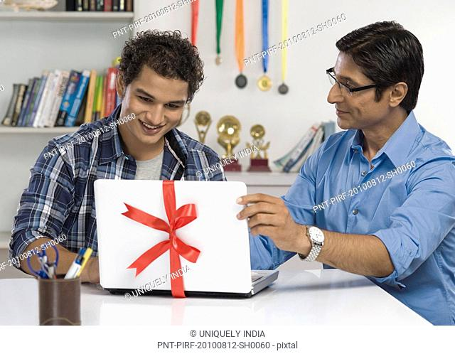 Man gifting a laptop to his son