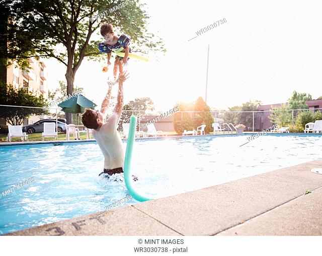 A man and a young boy playing in a swimming pool, the child being thrown up in the air