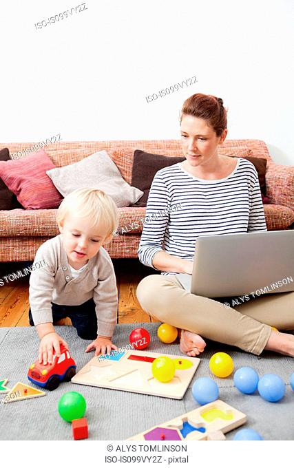 Mother using laptop, son playing