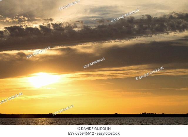 "Sunset over water from """"Delta del Po"""", Italian landscape. water and sky"