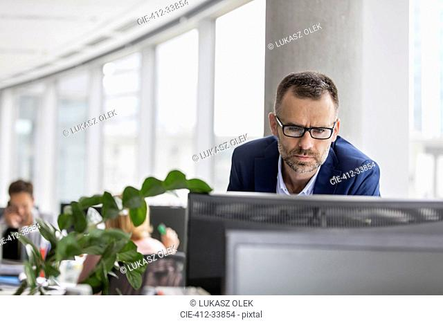 Serious businessman working at computer in office