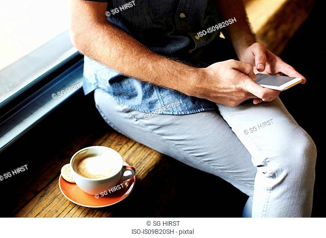 Mid section of young man sitting on cafe window seat texting on smartphone