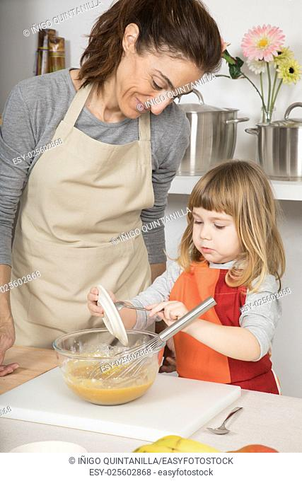 three years old child and woman, in teamwork, making and cooking a sponge cake at kitchen home, pouring grated lemon peel in glass bowl with whisk
