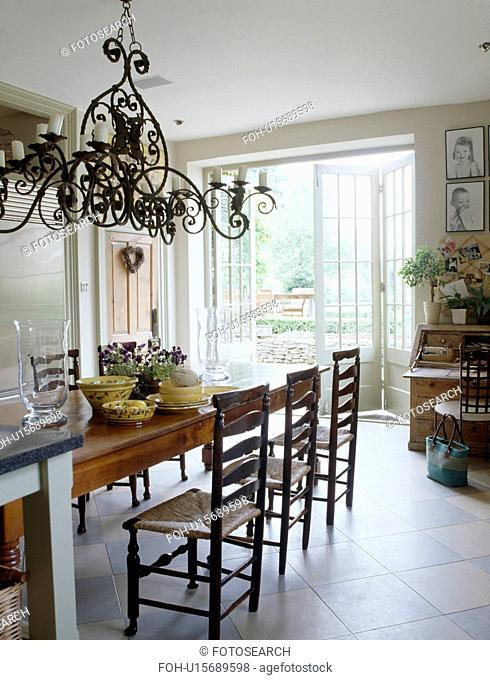 Ornate metal chandelier above table in dining room with white ceramic floor tiles
