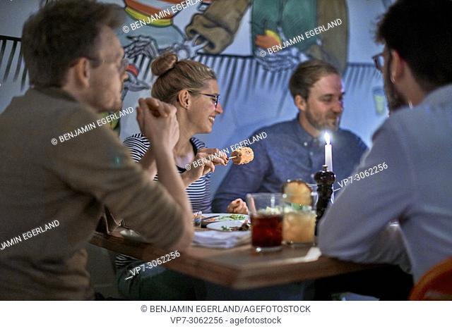 Friends in restaurant Blitz, Museumsinsel, near Isartor, Munich, Germany. South-African and vegetarian restaurant. German ethnicity