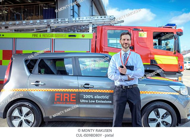 Portrait of fire chief in fire station with electric car