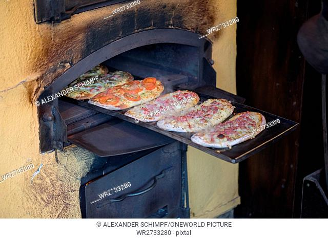 Switzerland, Basel city, Freshly baked, steaming flame cake on baking sheet in the open open, on the Christmas market